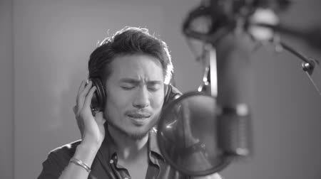 rehearsing : young asian singer singing in recording studio with headphone and microphone, black and white. Stock Footage