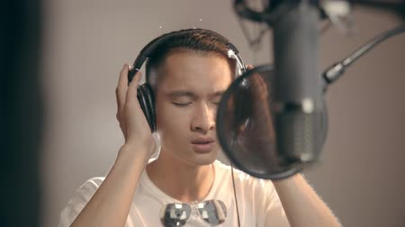 voz : young asian singer singing in recording studio with headphone and microphone.