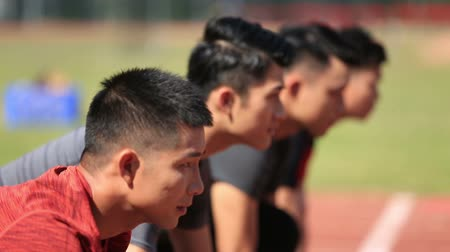 readiness : young asian adult sprinters on starting line, looking serious.