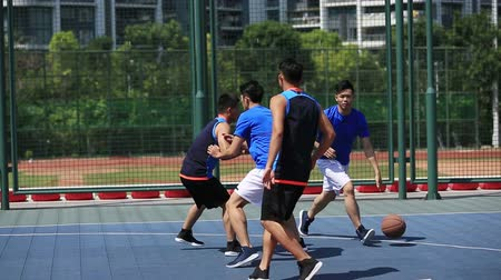 defending : asian young adults playing basketball on outdoor court.