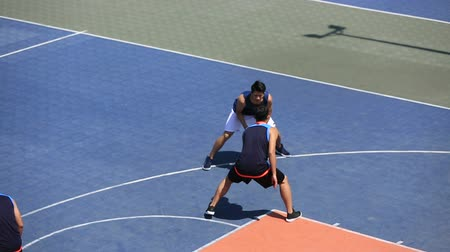 skorlama : young asian adults playing basketball on outdoor court, high angle view.