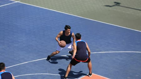 defending : young asian adults playing basketball on outdoor court, high angle view.