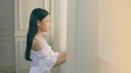 devět : nine-year-old beautiful little asian girl with black long hair looking out of window