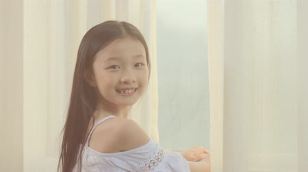 ski : beautiful 9-year-old little asian girl looking back and smiling to the camera in front of window