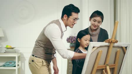 rehberlik : nine-year-old little girl making a painting with two parents standing behind watching encouraging and providing guidance Stok Video