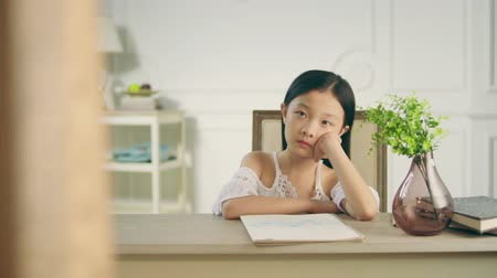 korejština : 9 year old little asian girl sitting in front of desk thinking