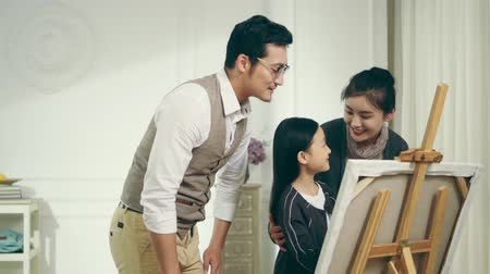 encouraging : nine-year-old little girl making a painting with two parents standing behind watching and encouraging Stock Footage