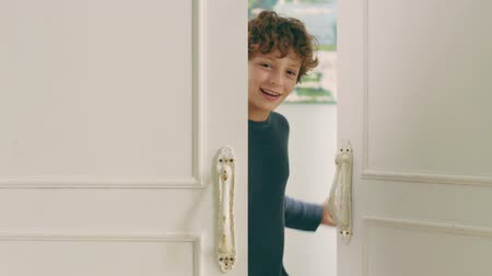coming home : little caucasian boy opening a door and saying hello Stock Footage