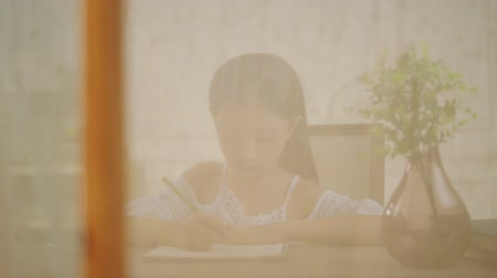 японский рисунок : nine-year-long little asian girl with long black hair sitting in front of window writing or drawing a picture
