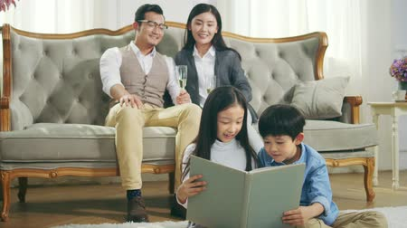 conta : two asian children sitting on carpet on the floor reading book with mother and father watching from behind Vídeos