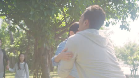 outdoor : lovely asian boy running toward father in park while walking with mother and sister