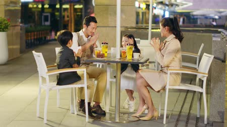 korejština : happy asian family with two children chatting relaxing at a coffee place