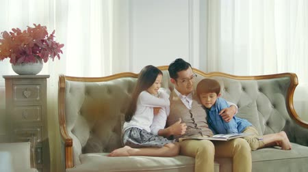 conta : loving asian father and two children reading book together in living room at home