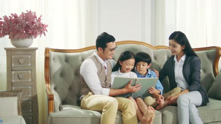 conta : asian family with two children reading book together in living room at home