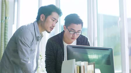 встреча : two young asian businessmen discussing business in office using desktop computer