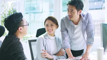 collaborating : a team of three young asian business people men and woman meeting in office Stock Footage