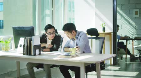 collaborating : two young asian business men working together in office of small company