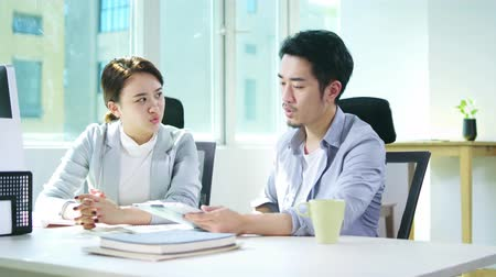 collaborating : young asian man and woman sitting at desk working together discussing business plan Stock Footage