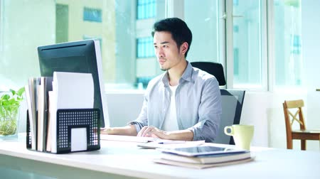 casual wear businessman : young asian business man working in office using desktop computer Stock Footage