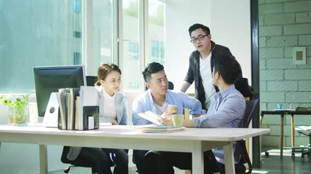 collaborating : four young asian businessmen and woman meeting in office discussing business in office of small company Stock Footage