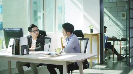 hong kong : two young asian men entrepreneurs discussing business in office of small company