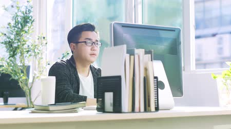colarinho branco : young asian business man sitting at desk in office working using desktop computer Stock Footage