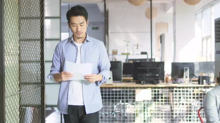 hong kong : young asian businessman looking at sales report while walking in office of small company