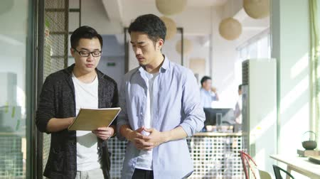 documentos : two young asian businessmen discussing business while walking in office of small company