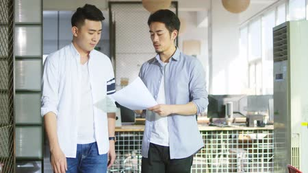 hong kong : two young asian businessmen analyzing sales report in office of small company