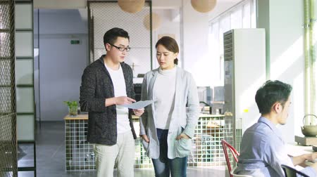 documentos : young asian businessman and businesswoman discussing sales report in office of small company Stock Footage