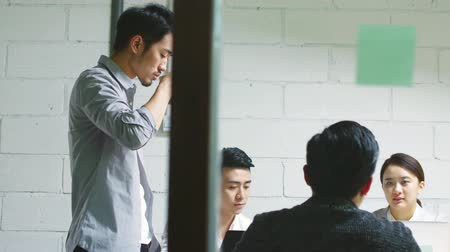colarinho branco : group of young asian entrepreneurs discussing business in company meeting room Stock Footage