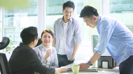hongkonger : four young asian people discussing business using tablet PC in office