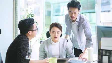 japonya : three young asian people discussing business using tablet PC in office Stok Video