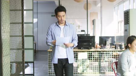 dokumentum : young asian entrepreneur reading report while walking in office