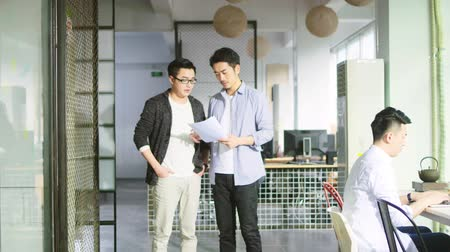 collaborating : two young asian business men discussing sales report whiling walking in office