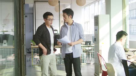 hongkonger : two young asian business men discussing sales report whiling walking in office