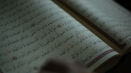 ислам : Turning a page of the holy Quran.