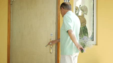 gizleme : An elderly man opens the door and gives a bouquet.