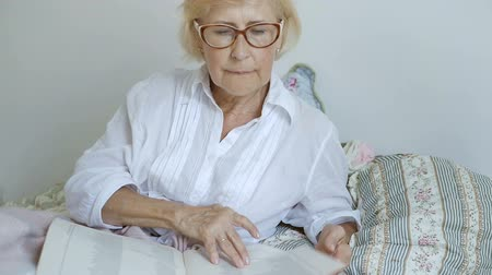 único : Elderly woman putting on glasses.