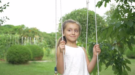 small park : The girl riding on a swing in the park Stock Footage