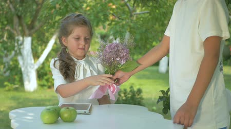 Войти : Boy gives a cute girl a flowers in the garden Стоковые видеозаписи