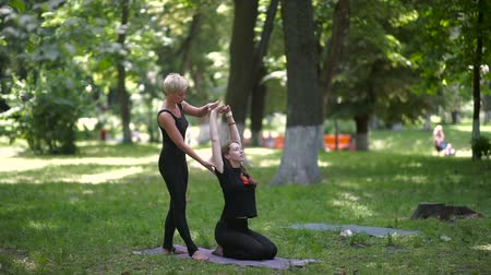gündelik kıyafetler : The trainer of yoga helps girls pull her hands.