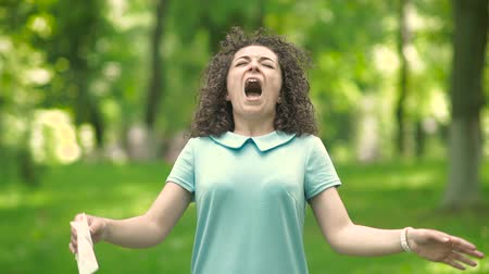 alerji : Young woman standing in a park sneezes. Stok Video
