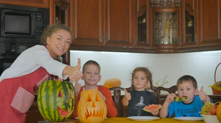 pumpkin pieces : Three cute children are eating the watermelon Stock Footage