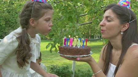 beijos : The girl blows out the candles on the cake
