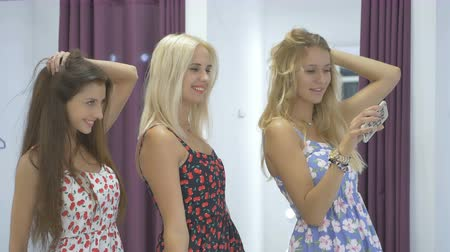 három ember : Three cute girl make selfie in mirror in showroom