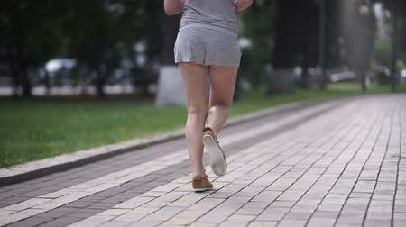 носить : Young curly girl with slim legs running in park
