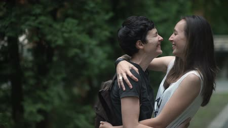 leszbikus : Two happy lesbians talks, hugs and kisses in park Stock mozgókép