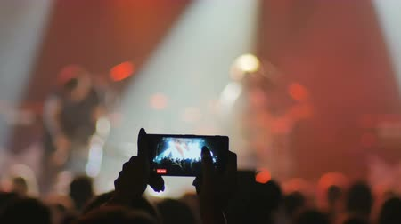 atirar : The fan make a video on a smartphone on a rock concert Stock Footage