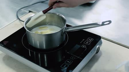 mashing : Milk and butter are heated in a saucepan Stock Footage